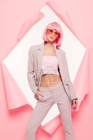 Photo pour Fille à la mode en costume, lunettes de soleil et perruque rose posant en papier déchiré, isolé sur blanc - image libre de droit