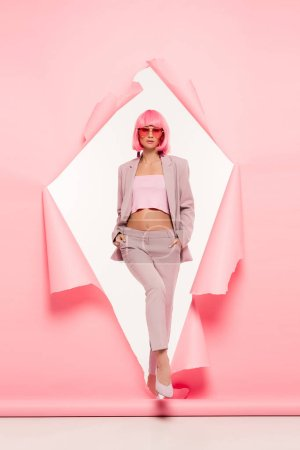 attractive fashionable girl in suit, sunglasses and pink wig posing in torn paper, on white