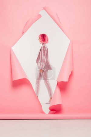stylish woman in suit and pink wig posing in torn paper, on white
