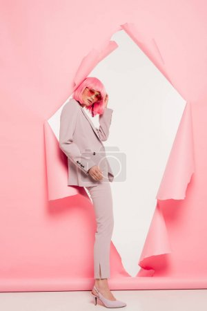 fashionable model in suit, sunglasses and pink wig posing in torn paper, on white