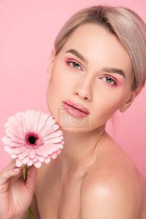 Photo pour Femme nue avec du maquillage rose tenant fleur, isolé sur rose - image libre de droit