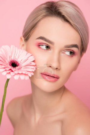nackte Mädchen mit rosa Make-up und Gerbera-Blume, isoliert auf rosa