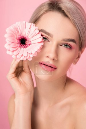 tender naked woman with pink makeup holding gerbera flower, isolated on pink