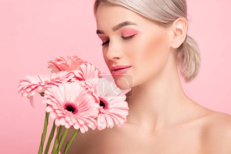 beautiful girl with closed eyes and pink makeup holding gerbera flowers, isolated on pink