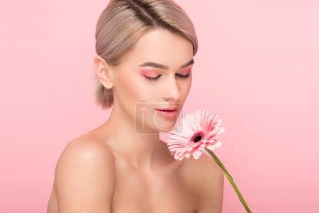 chica desnuda con los ojos cerrados sosteniendo flor de gerberas, aislado en rosa