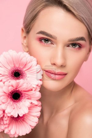 beautiful young woman with pink gerbera flowers, isolated on pink