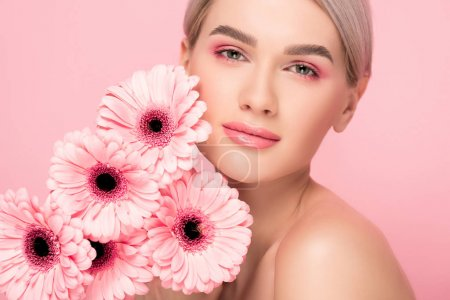 attractive girl with pink gerbera flowers, isolated on pink