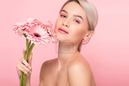 Photo for Naked girl holding pink gerbera flowers, isolated on pink - Royalty Free Image