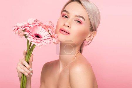 Photo pour Fille nue tenant des fleurs de gerbera rose, isolé sur rose - image libre de droit