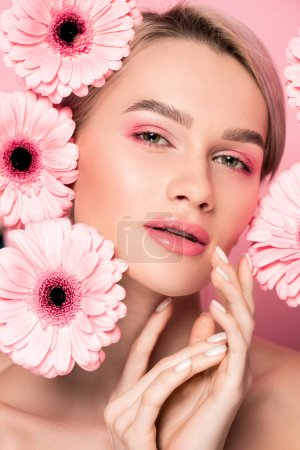 tender girl with makeup and pink gerbera flowers, isolated on pink