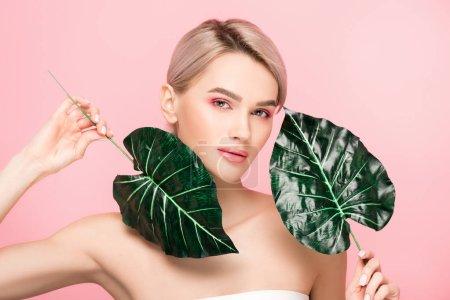 Photo pour Fille nue avec maquillage rose isolé sur rose avec des feuilles vertes - image libre de droit