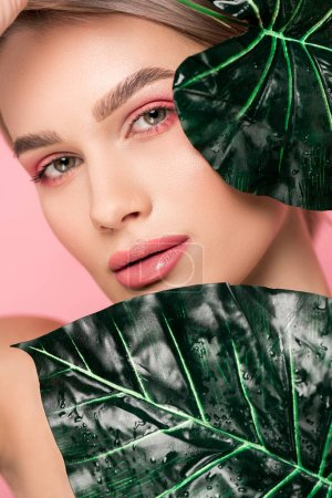 tender girl with pink makeup isolated on pink with green leaves