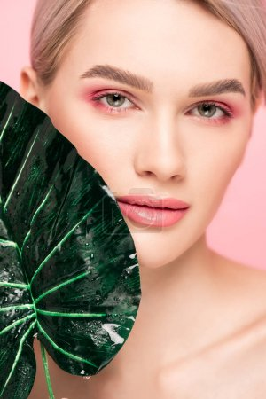 beautiful girl with pink makeup isolated on pink with green leaf