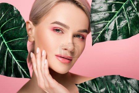 Foto de Atractiva chica tierna con maquillaje rosa aislada del rosa con hojas verdes - Imagen libre de derechos