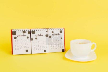 Photo pour Calendrier avec mois d'automne et tasse de café sur fond jaune - image libre de droit