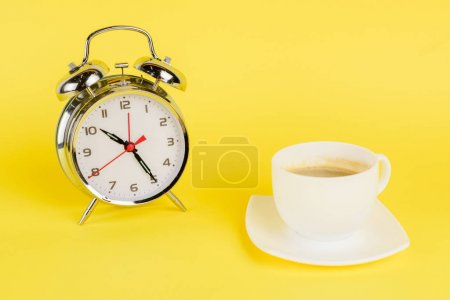 Silver alarm clock and cup of coffee on yellow background