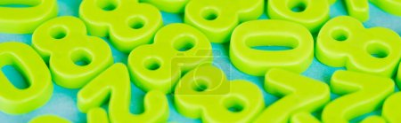 Photo for Panoramic shot of green plastic numbers on blue background - Royalty Free Image