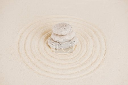 Stack of zen stones on sand surface with circles