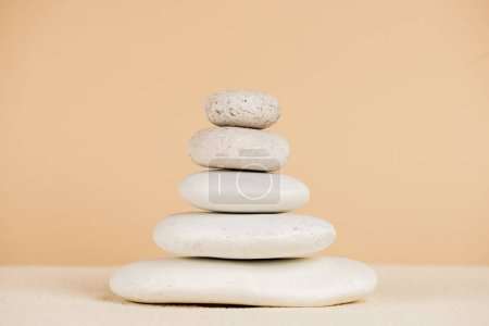 Close up view of stacked zen stones on sand isolated on beige