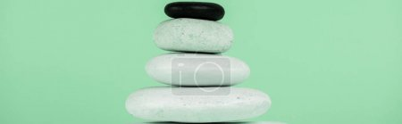 Panoramic shot of stacked zen stones isolated on green
