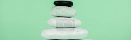 Photo pour Plan panoramique de pierres zen empilées isolées sur vert - image libre de droit
