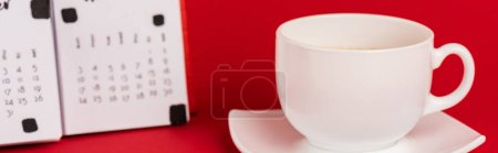 Photo for Panoramic shot of cup of coffee and calendar on red background - Royalty Free Image