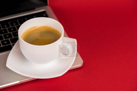 Photo for Close up view of cup of coffee on laptop on red surface - Royalty Free Image