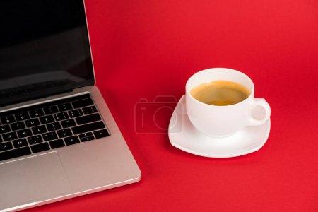 Photo pour Ordinateur portable avec écran vierge et tasse de café sur soucoupe sur fond rouge - image libre de droit