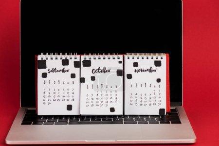Photo pour Calendrier avec mois d'automne sur ordinateur portable avec écran blanc sur fond rouge - image libre de droit