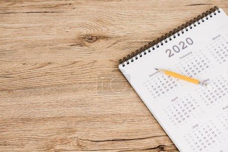 Photo pour Vue à grand angle du calendrier de l'année 2020 et crayon sur fond de bois - image libre de droit