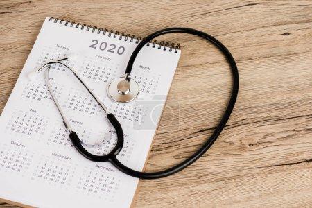 Photo pour Stethoscope et calendrier de l'année 2020 sur fond de bois - image libre de droit
