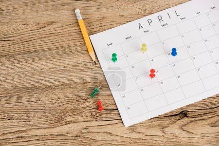 Photo pour Vue à grand angle du crayon, des épinglettes de bureau et du calendrier d'avril sur fond de bois - image libre de droit