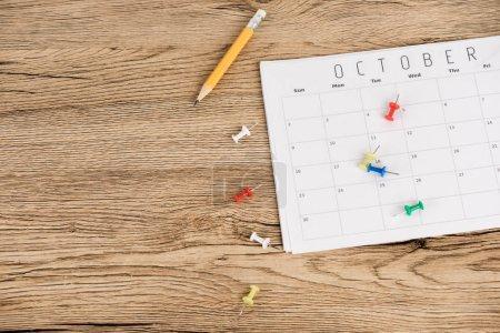 Photo pour Vue de dessus du crayon, des épinglettes de bureau et du calendrier d'octobre sur la surface en bois - image libre de droit