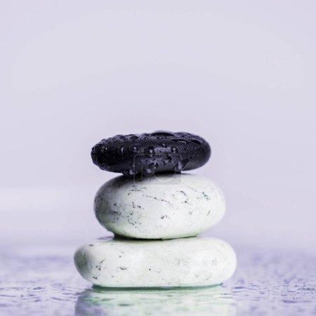 Photo pour Vue de près de douze pierres dans des gouttes d'eau sur verre humide isolées sur violet - image libre de droit
