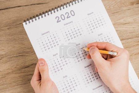 Photo pour Vue en croix de l'homme notant la date au crayon sur le calendrier sur fond de bois - image libre de droit
