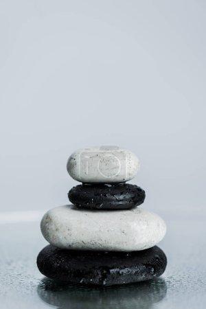 Photo pour Pierres zen blanches et noires sur verre mouillé isolées sur gris - image libre de droit