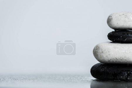 Photo pour Vue rapprochée de gouttes d'eau sur des pierres zen sur verre humide isolé sur gris - image libre de droit