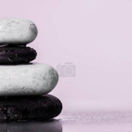 Photo pour Vue rapprochée des pierres zen humides sur verre avec gouttes d'eau isolées sur violet - image libre de droit