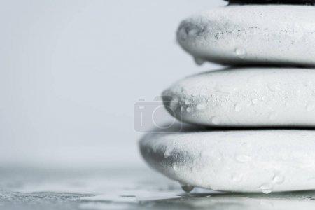 Photo pour Macro shot de pierres blanches zen dans des gouttes d'eau sur verre mouillé isolé sur gris - image libre de droit
