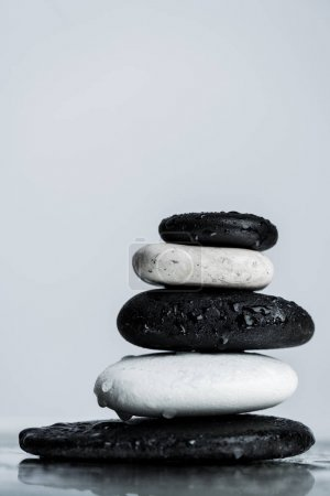 Close up view of stacked black and white zen stones on wet glass isolated on grey