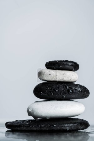 Photo pour Vue en gros plan de pierres zen noires et blanches empilées sur du verre humide isolées sur du gris - image libre de droit