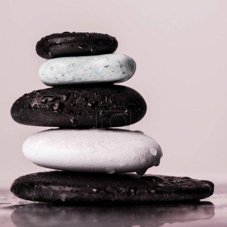 Photo pour Macro shot de pierres zen empilées dans des gouttes d'eau sur verre mouillé isolé sur rose - image libre de droit