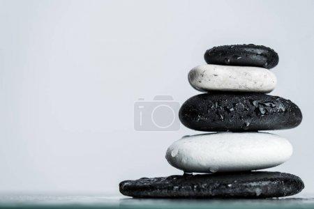 Photo pour Vue rapprochée de gouttes d'eau sur des pierres zen noires et blanches empilées sur du verre humide isolé sur du gris - image libre de droit