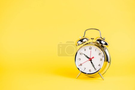 Photo for Silver alarm clock on yellow background - Royalty Free Image