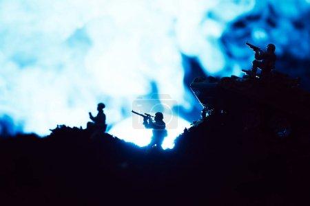 Photo pour Scène de combat avec des soldats en jouet et fumée avec la lune sur fond noir - image libre de droit