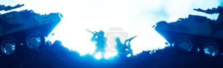 Foto de Juego de batalla con guerreros de juguete y tanques con iluminación en fondo azul, tiro panorámico. - Imagen libre de derechos