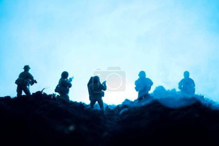 Photo for Toy soldiers with weapon and smoke on blue background, battle scene - Royalty Free Image