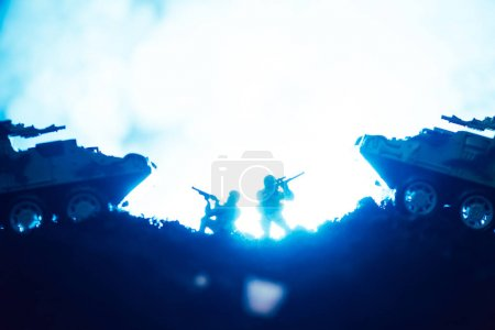 Photo for Battle scene of toy warriors and tanks with smoke on blue background - Royalty Free Image
