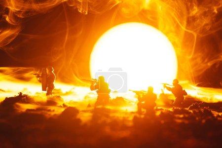 Photo pour Scène de combat de soldats jouets en fumée avec coucher du soleil en arrière-plan - image libre de droit