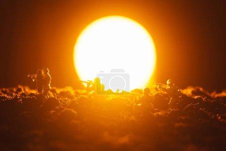 Photo pour Scène de combat de soldats jouets avec arme et coucher du soleil en arrière-plan - image libre de droit